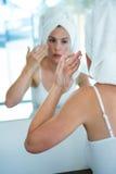kobieta stosuje twarzy śmietankę w lustrze Fotografia Royalty Free