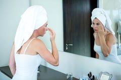 kobieta stosuje twarzy śmietankę w lustrze Zdjęcia Royalty Free
