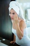 kobieta stosuje twarzy śmietankę w lustrze Zdjęcia Stock