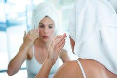 kobieta stosuje twarzy śmietankę w lustrze Zdjęcie Royalty Free