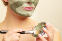 Kobieta stosuje z szczotkarską glinianą błoto maską jej twarz zdjęcia stock