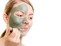 Kobieta stosuje z szczotkarską glinianą błoto maską jej twarz fotografia stock