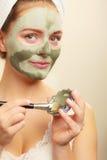 Kobieta stosuje z szczotkarską glinianą błoto maską jej twarz zdjęcie royalty free