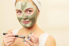 Kobieta stosuje z szczotkarską glinianą błoto maską jej twarz zdjęcia royalty free