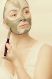 Kobieta stosuje z szczotkarską glinianą błoto maską jej twarz zdjęcie stock