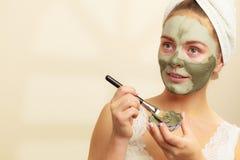 Kobieta stosuje z szczotkarską glinianą błoto maską jej twarz obrazy stock