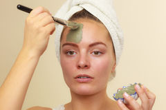 Kobieta stosuje z szczotkarską glinianą błoto maską jej twarz obraz stock