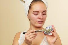 Kobieta stosuje z szczotkarską glinianą błoto maską jej twarz obrazy royalty free
