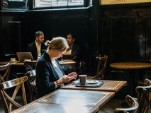 Kobieta studiuje mądrze telefon w national gallery kawiarni, Londyn Zdjęcie Royalty Free