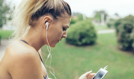 Kobieta słucha muzykę w smartphone z słuchawkami Fotografia Royalty Free