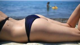 Kobieta sunbathing na plażowym lying on the beach na kamieniach zdjęcie wideo