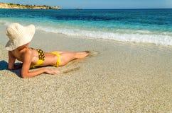 Kobieta sunbathing na plaży Zdjęcie Royalty Free