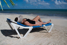 Kobieta sunbathing przy plażą z dużym słomianym kapeluszem obraz royalty free