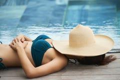 Kobieta sunbathing przy poolside fotografia stock