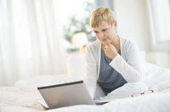 Kobieta surfing Na laptopie W sypialni Obrazy Royalty Free