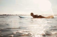 Kobieta surfingowiec unosi się na długim surfboard w kierunku * zdjęcia stock