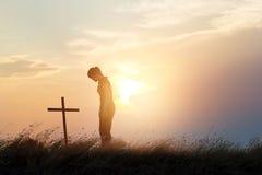 Kobieta szanuje przy krzyżem na polu zmierzchu tło Fotografia Stock