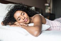 Kobieta szczęśliwa na łóżkowej ono uśmiecha się i rozciąga patrzeje kamerze w t obraz stock