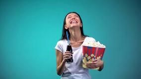 Kobieta szczerze śmia się dopatrywanie komedię z filiżanką popkorn i soda, zabawa obrazy stock
