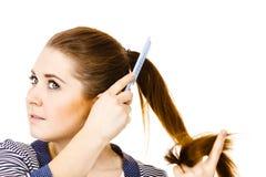 Kobieta szczotkuje jej długie włosy używa gręplę Obrazy Royalty Free