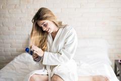 Kobieta szczotkuje jej włosy w łóżku Obrazy Stock