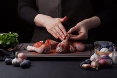 Kobieta szef kuchni naciera jej paprykę z świeżymi surowymi kurczaków drumsticks na ciemnym tle Niedaleki kłamstwo składniki dla Fotografia Stock