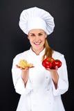 Kobieta szef kuchni nad ciemnym tłem z pomidorami i makaronów kluskami Zdjęcie Royalty Free