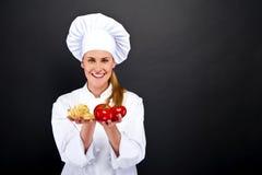 Kobieta szef kuchni nad ciemnym tłem z pomidorami i makaronów kluskami Zdjęcia Stock