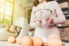 Kobieta szef kuchni odsiewa mąkę, ugniata ciasto Piekarnia lub Wypiekowy pojęcie ciasta jajka mąki składniki Obrazy Royalty Free
