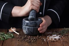 Kobieta szefa kuchni ubijanie ziele w moździerzu dla karmowego kucharstwa na czarnym tle i pikantność Fotografia Royalty Free