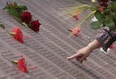Kobieta szukał imię jej krewni w pamięci ściany pamiątkowym grób w Mallorca obrazy stock