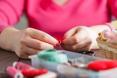 Kobieta szy czerwony serce kształtującą zabawkę igłą Obrazy Royalty Free