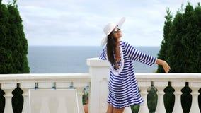 Kobieta tanczy w kapeluszu i okularach przeciwsłonecznych mieć zabawa plenerowego tarasowego balkon z antykwarskim białym poręcze zbiory