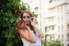 Kobieta target598_0_ na telefon komórkowy, przyglądający puszek. Przewyższa Obraz Stock