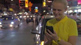 Kobieta texting na komórce i patrzeje noc Bangkok, Tajlandia zdjęcie wideo