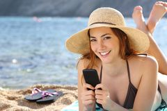 Kobieta texting w mądrze telefonie na wakacjach na plaży zdjęcia stock