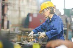 Kobieta Tnący metal w garażu zdjęcia royalty free