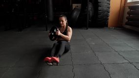 Kobieta trenuje abs, trzyma wewnątrz wręcza ciężar od barbell w zwolnionym tempie zbiory