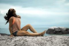 Kobieta trzepocze jej włosy na skale przy zmierzchem na Bakovern plaży, Kapsztad obrazy stock