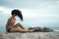 Kobieta trzepocze jej włosy na skale przy zmierzchem na Bakovern plaży, Kapsztad obraz royalty free