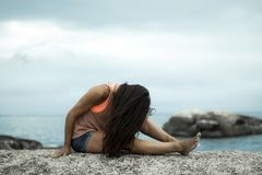 Kobieta trzepocze jej włosy na skale przy zmierzchem na Bakovern plaży, Kapsztad zdjęcia royalty free