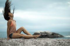Kobieta trzepocze jej włosy na skale przy zmierzchem na Bakovern plaży, Kapsztad zdjęcia stock