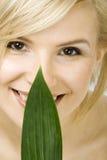 Kobieta trzyma świeżego zielonego liść przy jej twarzą zdjęcie royalty free