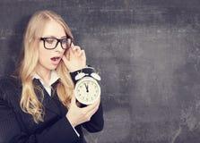 Kobieta trzyma alarmclock Blackboard tło zdjęcia stock
