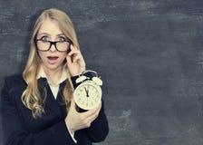 Kobieta trzyma alarmclock Blackboard tło zdjęcie royalty free