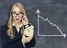 Kobieta trzyma alarmclock blackboard tło z diagramem zdjęcie stock