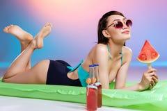 Kobieta trzyma arbuza kawałek w okularach przeciwsłonecznych podczas gdy relaksujący na pływackiej materac Obrazy Stock