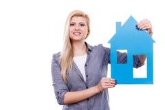 Kobieta trzyma błękitnego papieru domu modela wycinankę Zdjęcie Stock