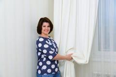 Kobieta trzyma białą zasłonę na okno Obraz Royalty Free