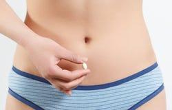 Kobieta trzyma bia?? pigu?k? przeciw jej nagiemu cia?u Dieta nadprograma poj?cie Na bielu zdjęcie stock